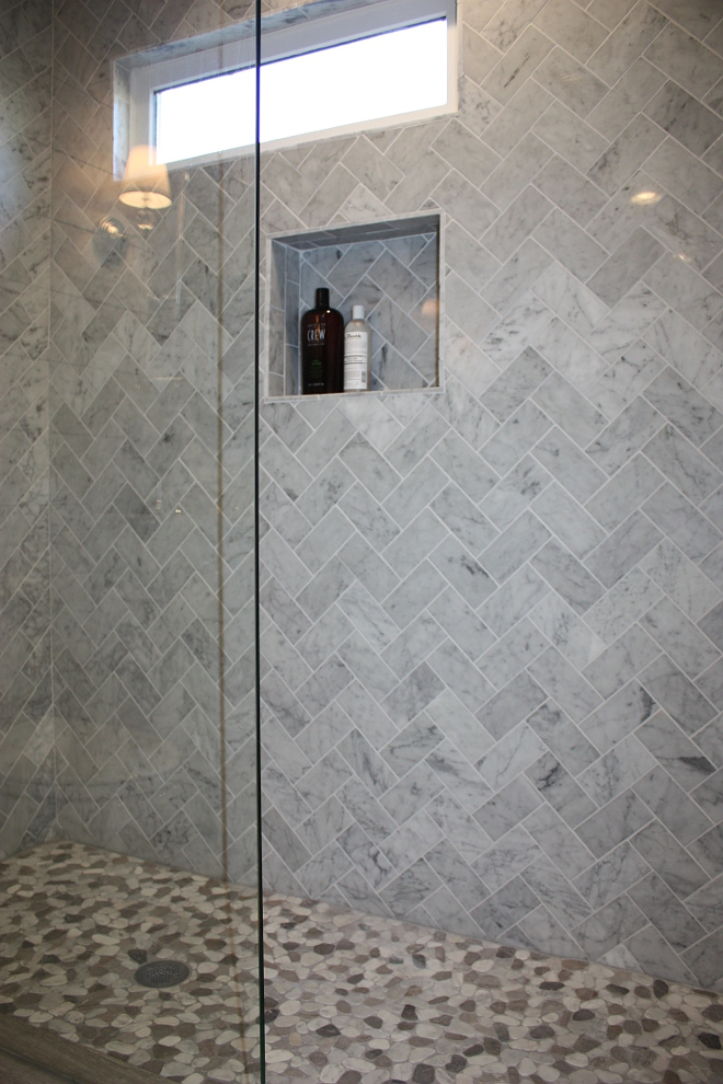 Herringbone marble tile with pebble floor tile shower