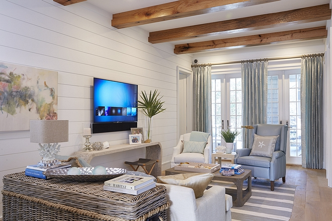 Coastal family room feels relaxed and very beach-y. Notice the wide plank hardwood floors, ceiling beams and shiplap walls