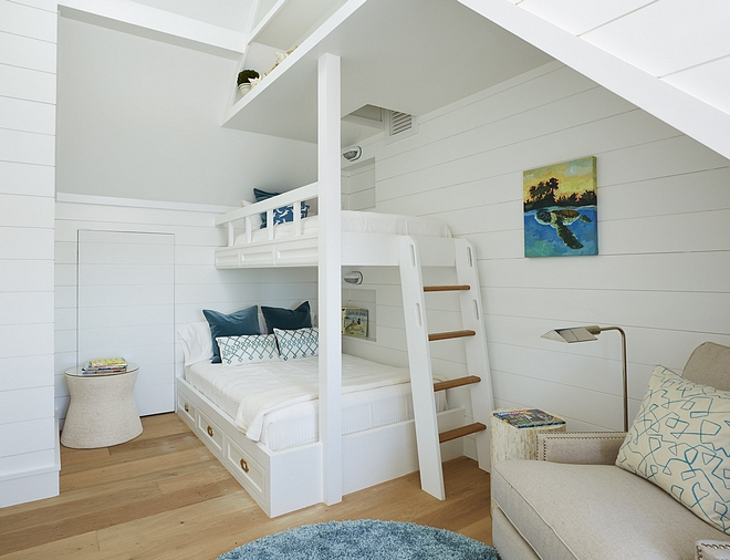 Bunk room features shiplap and custom storage above bunk beds