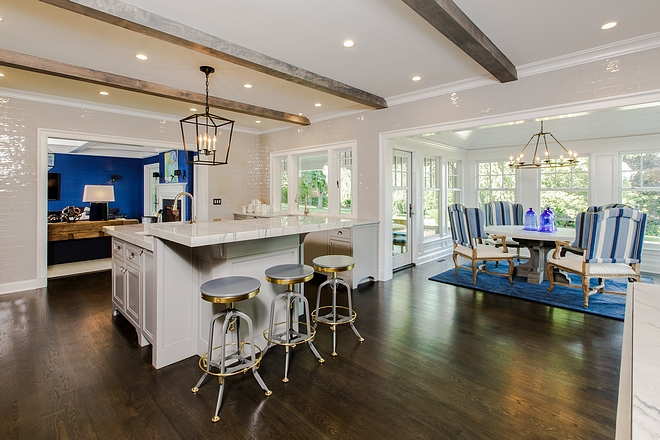 Kitchen opens to a breakfast room and family room Notice the floor-to-ceiling grey tile and ceiling beams