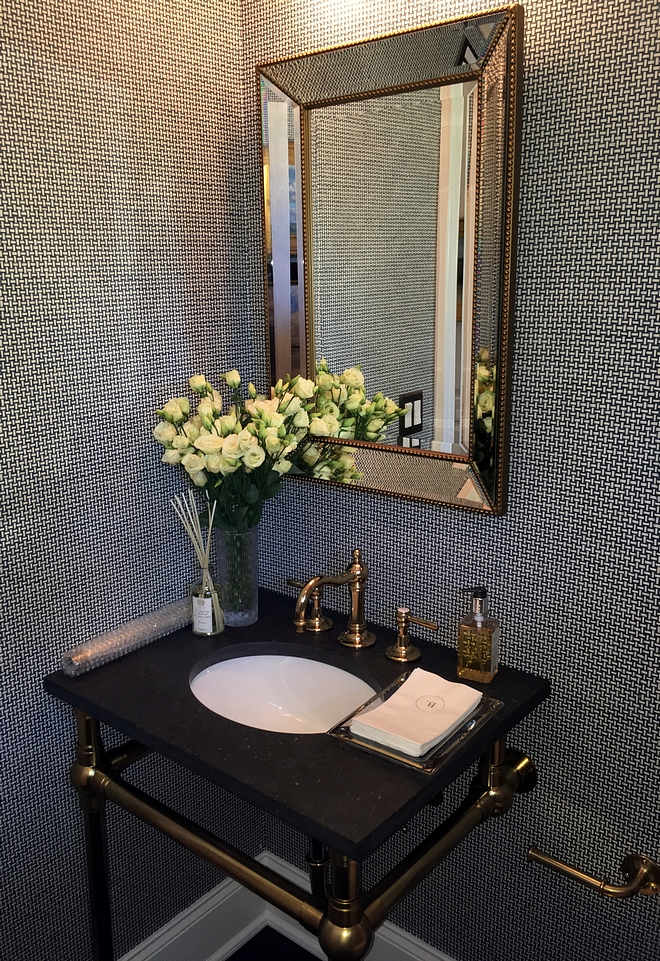 Powder room This powder room features a textured wallpaper and brass fixtures, including a brass washstand with black granite countertop