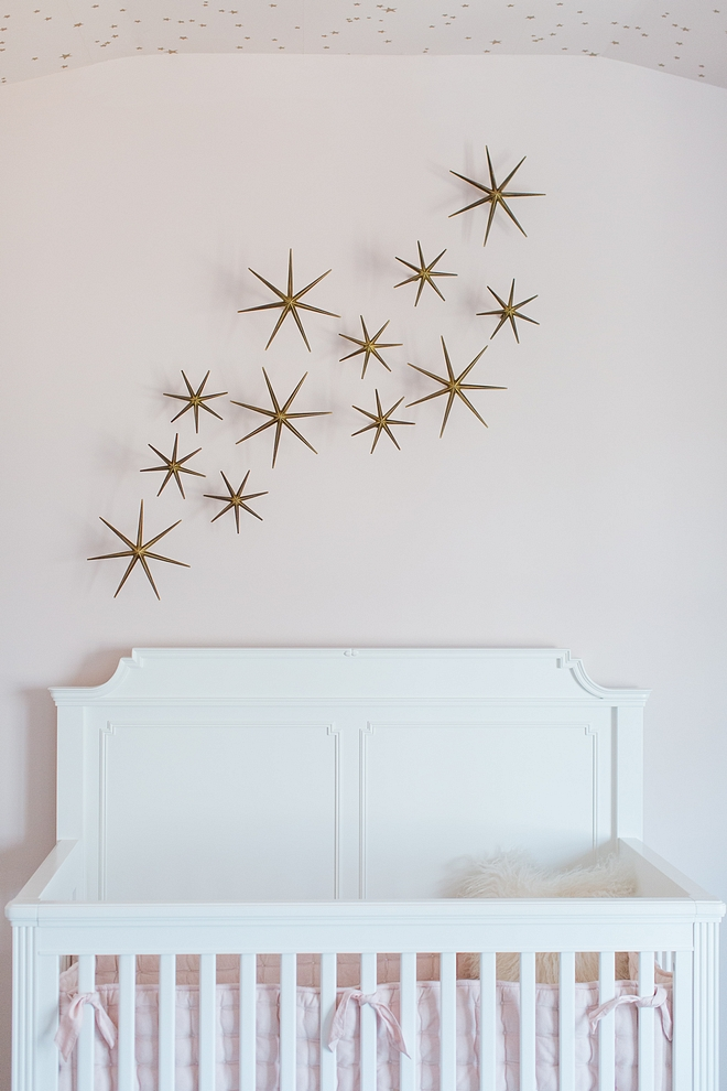 Pale pink nursery with white crib, Stone & Leigh Built To Grow Crib, and metal star wall decor