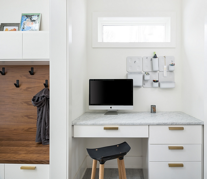 The mudroom features a custom desk with Carrara marble countertop On the left you will find the mudroom with Walnut bench
