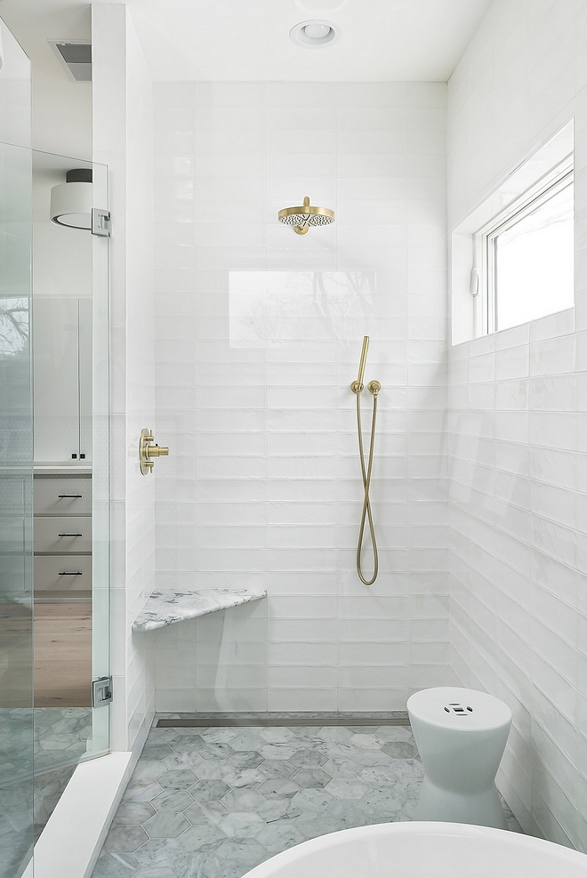 "Bathroom tile Bathroom tiles are carrara 6"" hex tiles on floor with a linear drain Subway long subway tiles have been stacked for a modern look These are glossy white with a wavy texture"