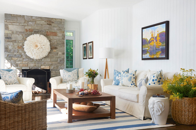 Country Coastal Living Room This country coastal living room sets the vibe for this lake cottage with colorful decor, vertical shiplap and that gorgeous stone fireplace