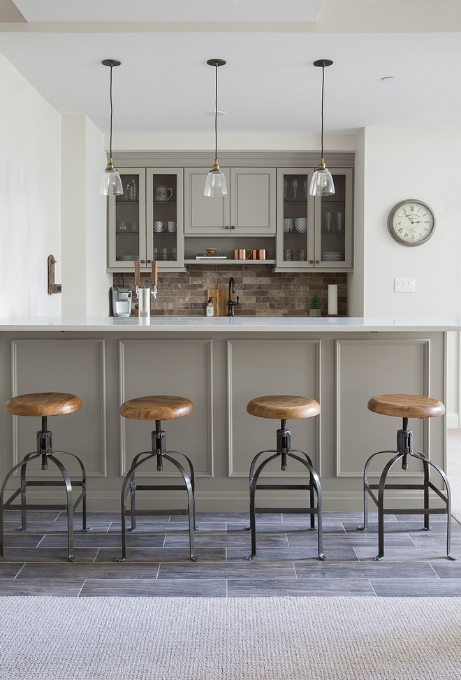 Basement features a grey bar, brick-style backsplash and wood-looking floor tile similar cabinet paint color Benjamin Moore Ozark Shadows