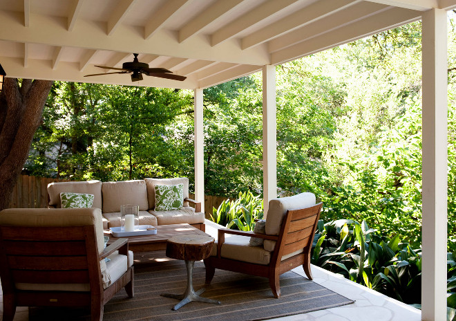 Farmhouse porch with Teak patio furniture and surrounded by plants