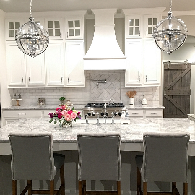 White Farmhouse Kitchen White Farmhouse Kitchen with Superwhite quartzite countertop and clear glass globe chandeliers White Farmhouse Kitchen
