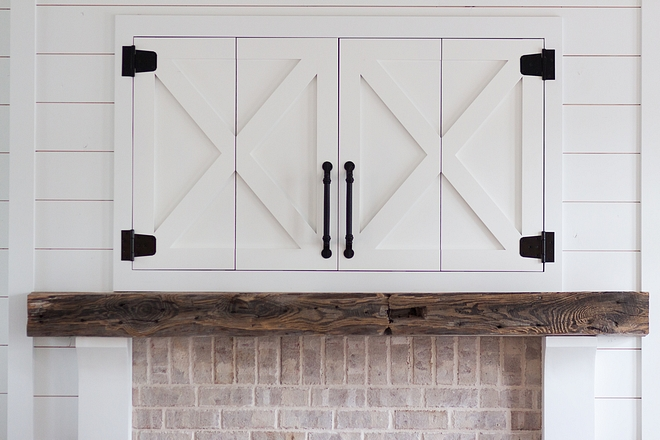 Barn door tv cabinet above fireplace The TV is concealed in the custom farmhouse-inspired cabinet above the fireplace source on Home Bunch