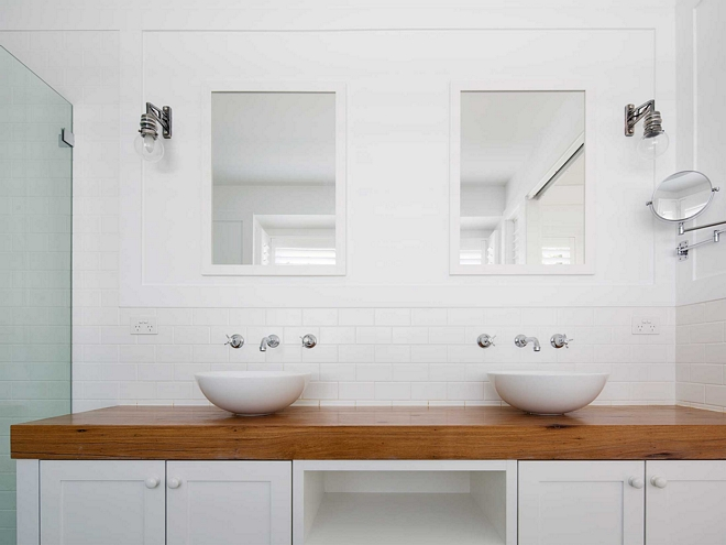 Round bathroom vessel sinks on top of thick wood countertop - clean timeless look