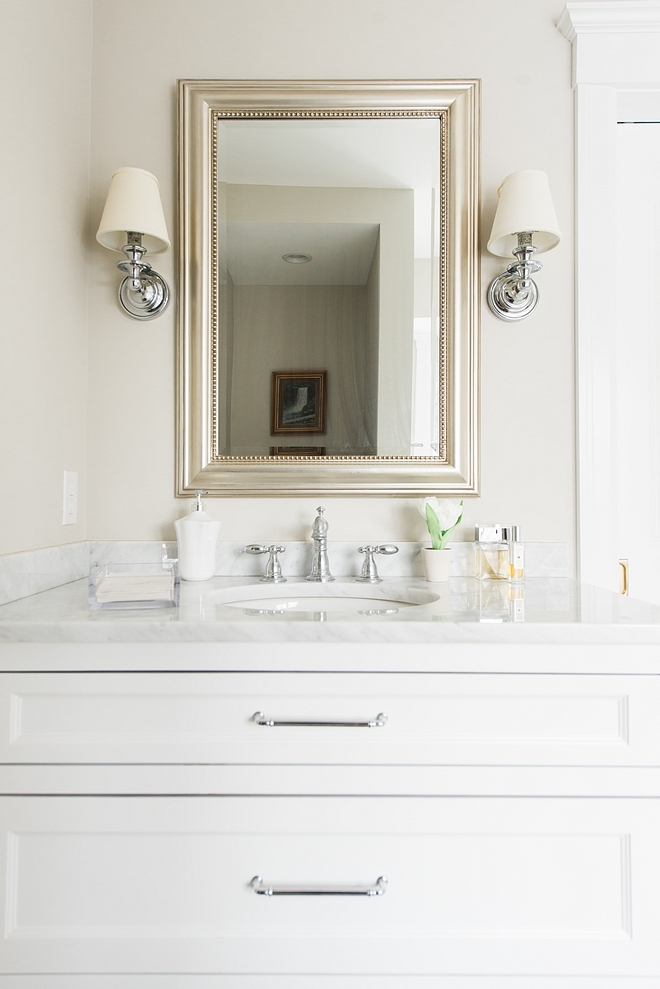 Classic white bathroom vanity with white marble countertop polished nickel hardware and polished nickel sconces flanking mirror