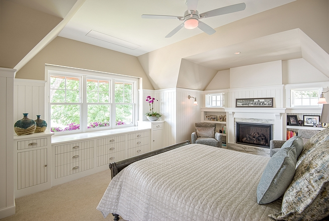 Beadboard bedroom The homeowner liked the idea of irregular ceilings, reminiscent of grandmother 's attic Recessed bookshelves flank a fireplace to create a cozy reading area Deep window boxes add a pop of color