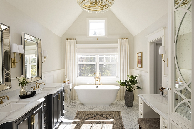 Bathroom The designer appointed this room with grandeur by nestling the master bathroom within the home's peaked roofline Beside the makeup vanity we designed custom storage with a mirrored finish and curved detailing #bathroom