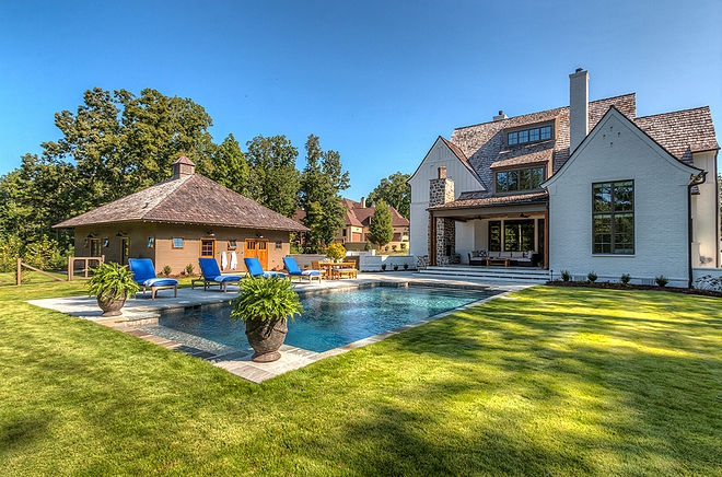 Backyard with pool Carriage house and painted brick home