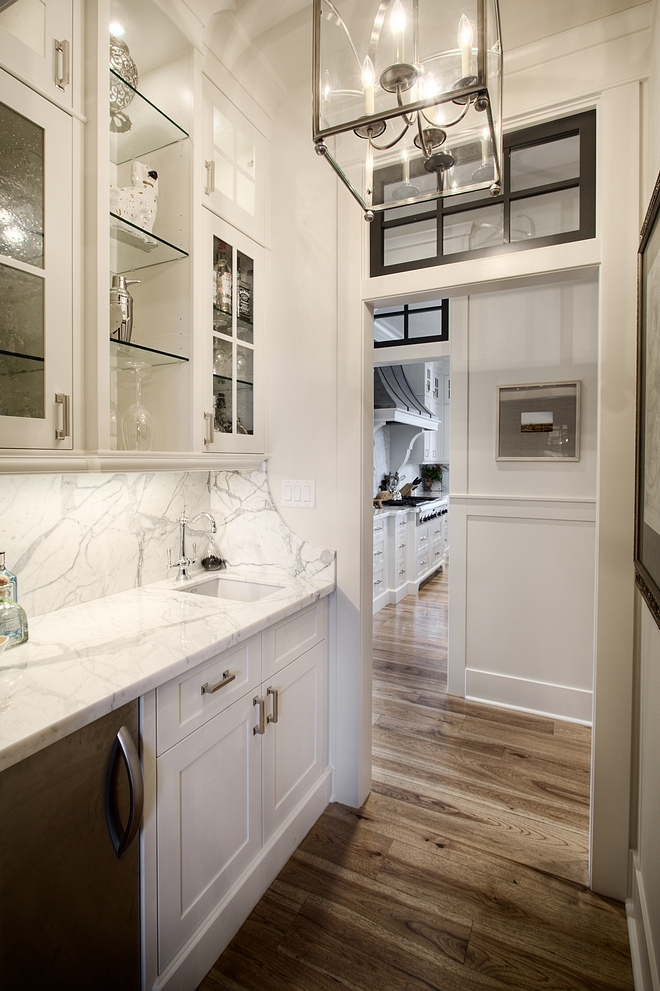 Butlers pantry with white cabinets painted in Benjamin Moore White paint color hardwood floors transom window above doorway and Statuario marble countertop and marble slab backsplash #butlerspantry