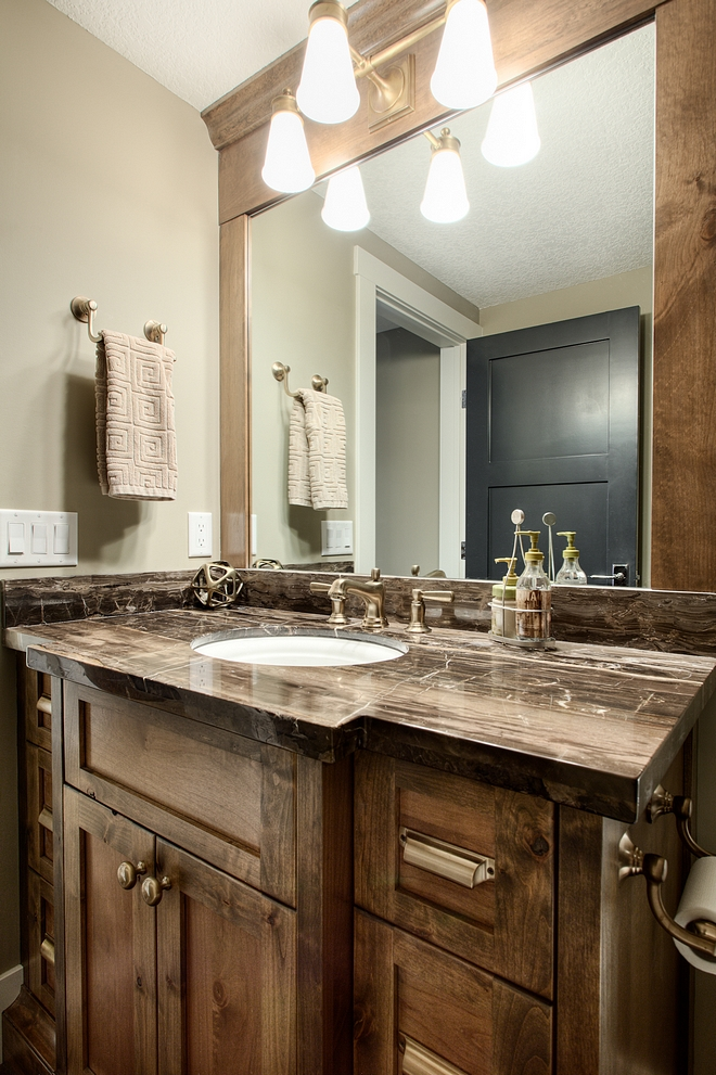 Basement bathroom features Alder cabinetry and a dark marble countertop #basementbathroom