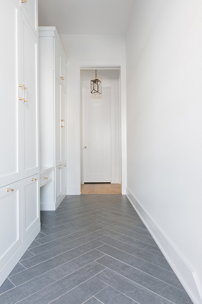 Mudroom features grey tile in a herringbone pattern and white cabinets