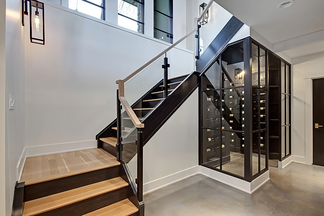 Basement Modern Staircase leading to a wine enclosure with black steel doors #modernstaircase #wineenclosure