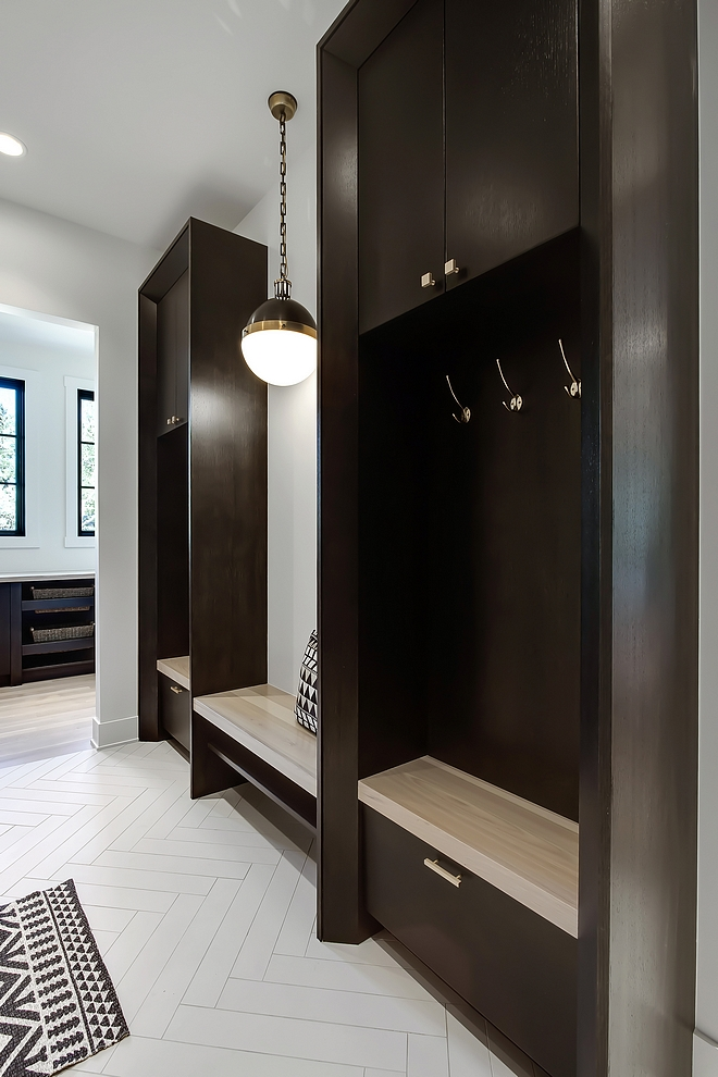 Mudroom The main level mudroom features custom built-on-site 1⁄4 sawn oak lockers and shelves for shoe storage. Flooring is an oversized porcelain tile in a herringbone pattern #mudroom #mudroomlockers #mudroomflooring