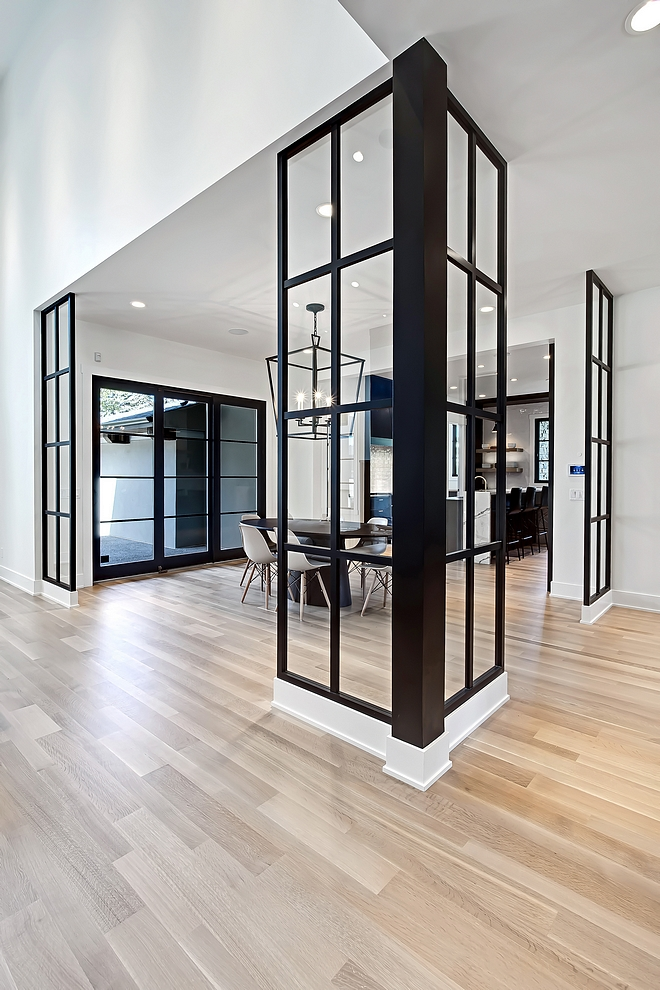 The breakfast nook features glass and lacquered dividers This space is viewed right when you walk into the home and the designer defined the space with these custom dividers #interiorideas #interiordesignideas #roomdividers #blackandwhite #blackwindows