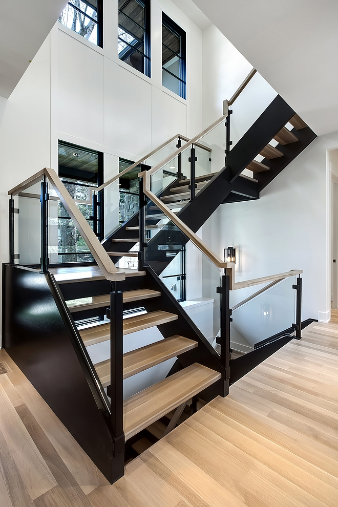 Modern Staircase The staircase is a combination of custom iron post in a matte black finish, 10 mm glass panels and a 1/4 sawn oak handrail. It goes perfectly with the black stringers and natural finish hardwood treads Custom designed hickory square handrail, iron post & glass panel railing #ModernStaircase #Staircase