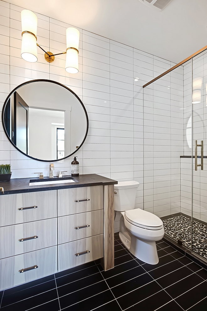 Bathroom with 4x16 white subway tile in a horizontal stack pattern on walls and 4x16 black subway tile in a stack pattern on floors #bathroom #4x16subwaytile #stacktilepattern #stacktile #stackpattern