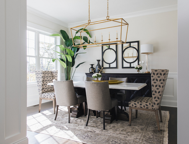 Dining Room Decor The dining room wainscoting gives it a classically formal feel but the gilded iron linear light fixture makes it fresh and inviting #diningroom #decor #diningroomdecor