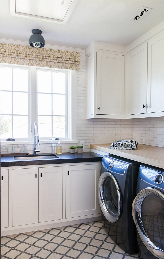 Laundry room with off white cabinets Cabinet Paint Color Farrow and Ball 2001 Strong White and two types of countertop Leathered Black Granite by sink and White Oak over washer and dryer #laundryroom