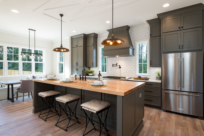 Grey Farmhouse Kitchen Staying true to the modern farmhouse style, we choose the green/grey custom colored cabinets The ceiling trim accents (above pendants) were crafted to look like a traditional barn door #GreyFarmhouseKitchen
