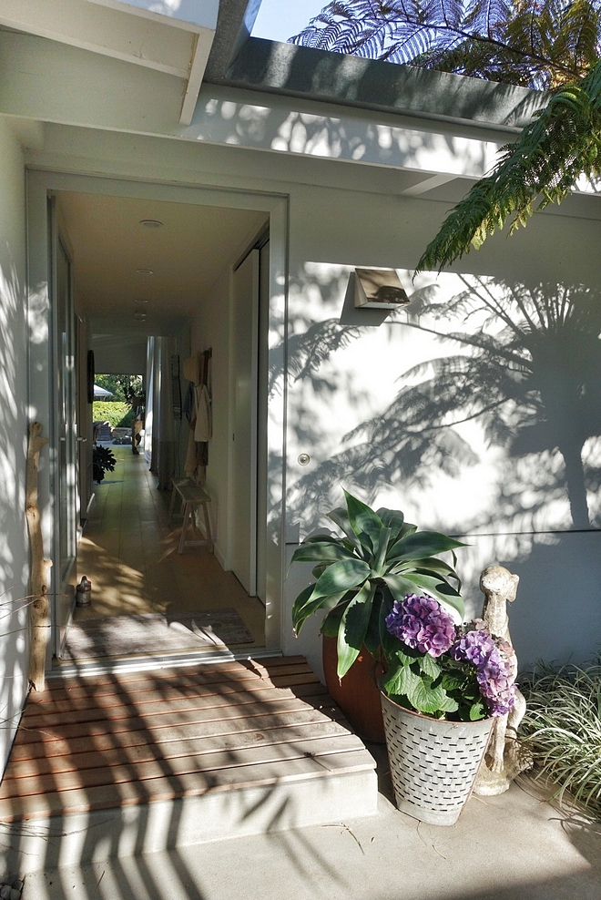 Ranch Home Ranch Home Front Door Foyer An aluminum and glass front door opens to a long hall leading to the main rooms with direct view to the lush backyard #Ranchhome #foyer #frontdoor #hall #aluminumdoor