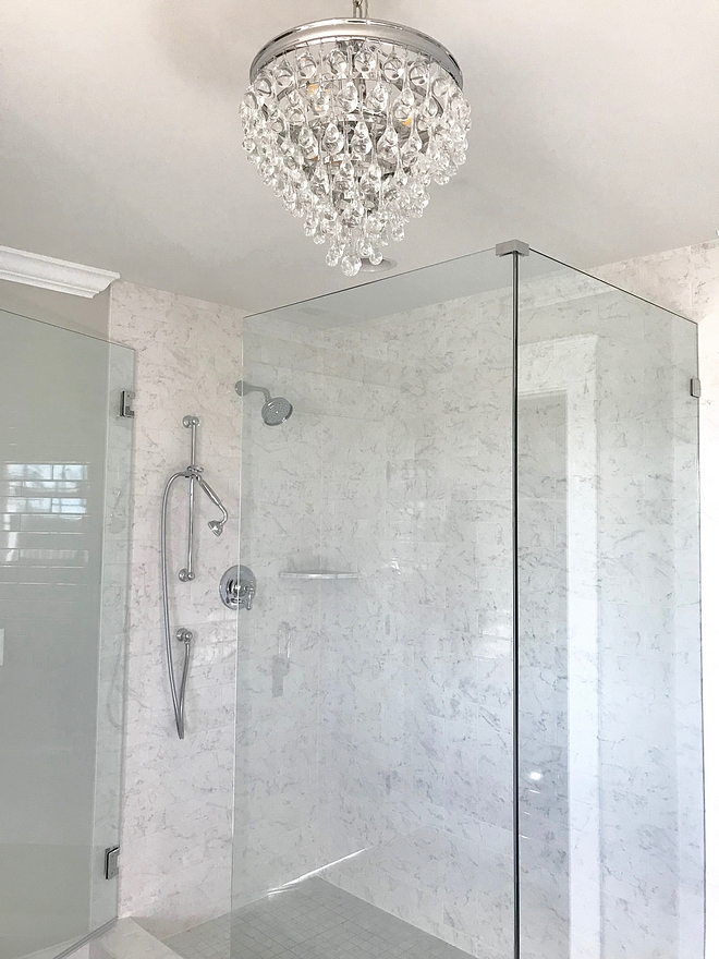 White Marble Shower The shower tile is from the EON Carrara collection from Atlas Concorde The grout on the walls is white The grout on the floor tiles is Rolling Fog We used a white Schluter edge for a clean finish on the rough ends of the tiles All the showers in the house have frameless glass walls and doors White Marble Shower #WhiteMarbleShower