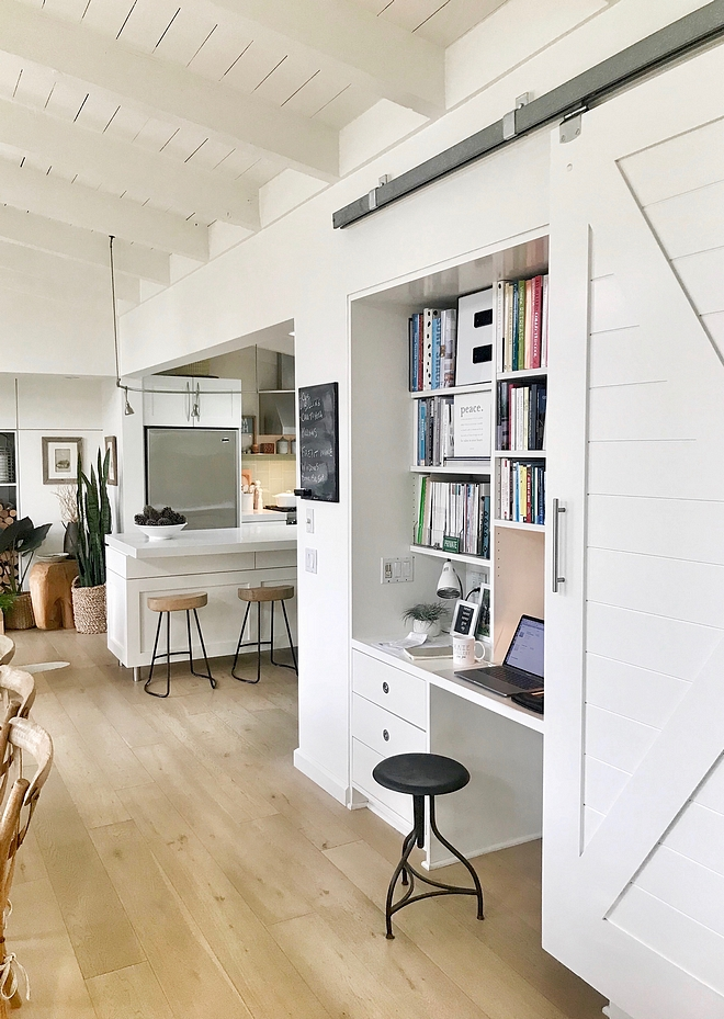 Built in Desk A white barn door conceals a practical built-in desk with built-in bookshelves that serves as the main home office Small Spaces Small Interiors #barndoor #builtindesk #builtins #smallspaces #samllinteriors