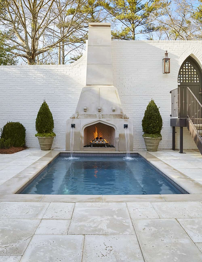 Pool with Fireplace Limestone pool surround The cocktail pool is flanked by two dramatic bronze fountain scuppers and a beautifully designed limestone fireplace adorned with limestone fireballs #Pool #poolFireplace #Limestone #poolsurround