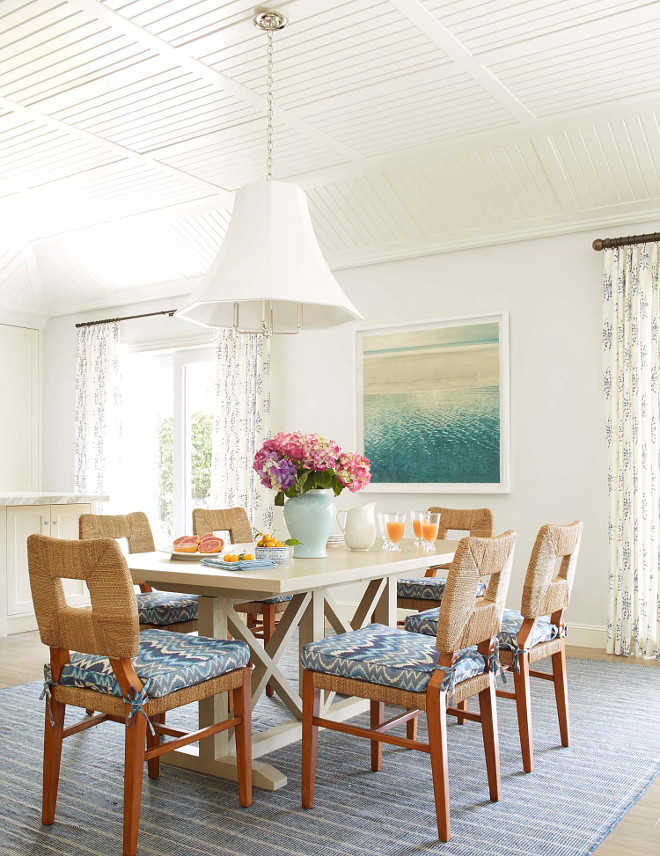 Coastal Dining Room with off white walls, painted in Paper White by Benjamin Moore, striped blue rug, light wood dining table and paneled ceiling vaulted tongue-and-groove ceiling #CoastalDiningRoom #offwhitewalls #PaperWhitebyBenjaminMoore