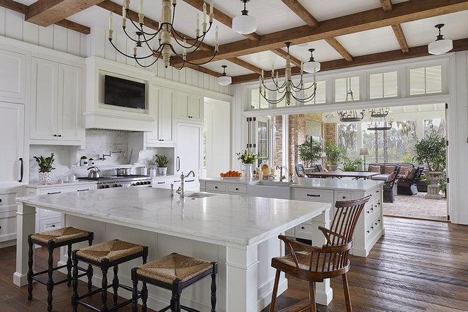Kitchen The spacious kitchen has two large marble-topped islands, perfect for entertaining. A sixteen foot bifold door opens to the screened porch, allowing the homeowners to take advantage of the breeze while also creating a seamless transition between inside and out #kitchen #whitekitchen #kitchendoor #patiodoor #kitchens