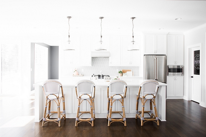 This kitchen looks too bright/stark here due the photography adjustments, but this kitchen is, in fact, well-balanced with the white cabinets, grey backsplash tile and dark hardwood flooring