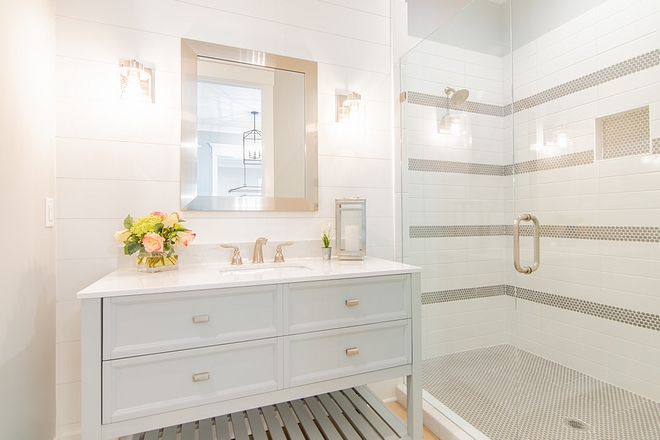 Bathroom with white shiplap accent wall painted in SW Extra White light grey vanity and shower with striped tile design #bathroom