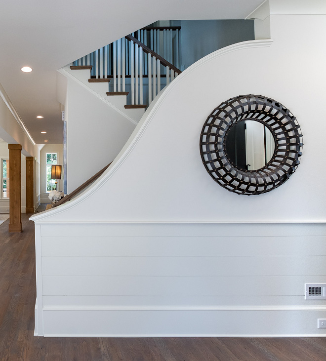 Foyer Wainscoting We didn't want to have to walk in and see a boring stair railing and balusters, so we opted for this one of a kind curved railing that hides the stairway just enough and provides for a WOW factor upon entering the home Shiplap wainscoting was a must #Wainscoting #Staircasewainscoting #FoyerWainscoting