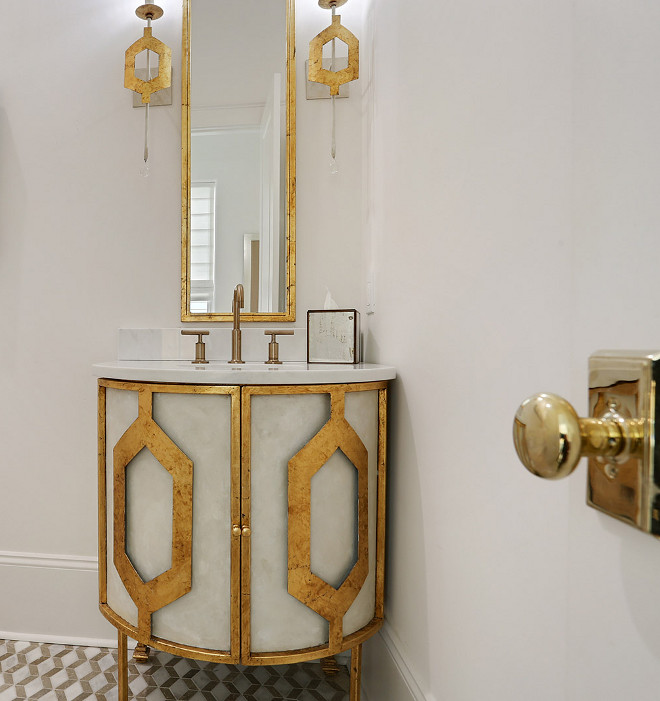 Powder room vanity Powder room features a stunning custom vanity cabinet, mirror and sconces. They are fabricated and painted in a cream whitewash finish with gold trim #Powderroom #Powderroomvanity