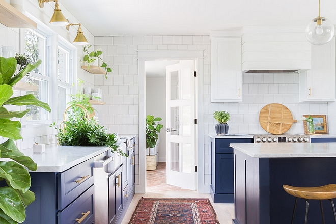 Kitchne The thoughtfully-chosen cabinetry colors, classic square subway tile, modern brass hardware and custom white oak floating shelving bring a bit of fun and whimsy to this classic kitchen #kitchen #cabinetrycolors #classictile #squaresubwaytile #modernbrasshardware #classickitchen 2540 Love ©AlyssaRosenheck