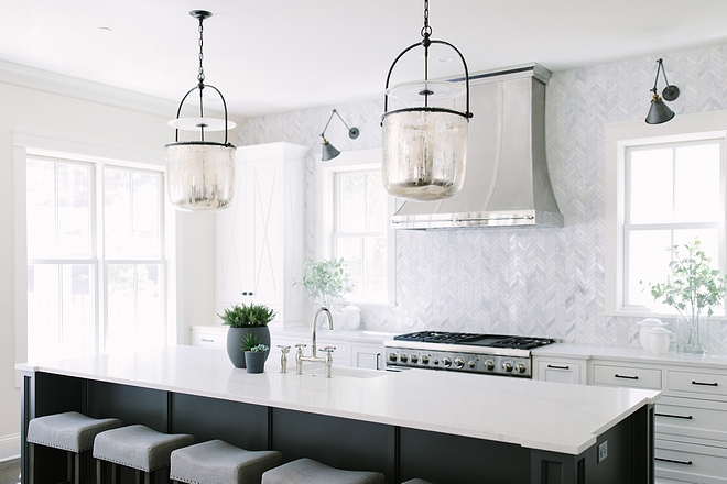 Kitchen features white perimeter cabinets, charcoal gray island , beautiful pendant light and chevron backsplash tile #kitchen #whitekitchen #kitchenpendantlight #countertop #charcoalisland #chevronbacksplash