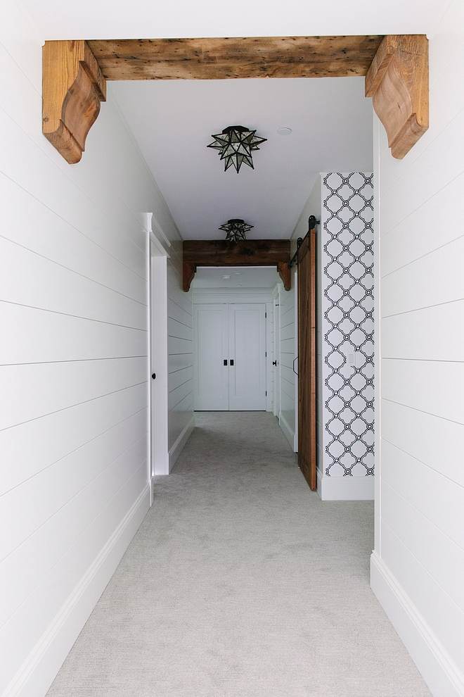 The basement features shiplap walls, painted in Benjamin Moore Simply White and rustic ceiling beams The exposed beams are actually barn wood that the designer covered duct work to disguise it They had the barn wood corbels made of real barn beams #beans #barnwood #reclaimedbeams #basement #shiplap