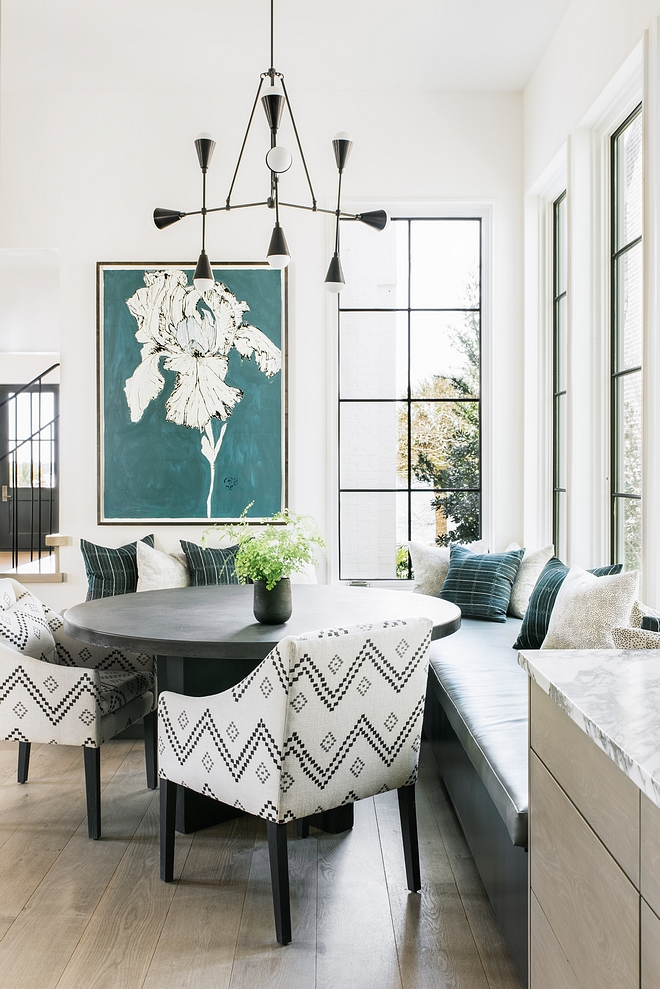 Modern Breakfast Nook with black framed windows, modern chandelier and a large l-shape banquette #BreakfastNook #ModernInteriors #Modernhomes #Modernchandelier #banquette