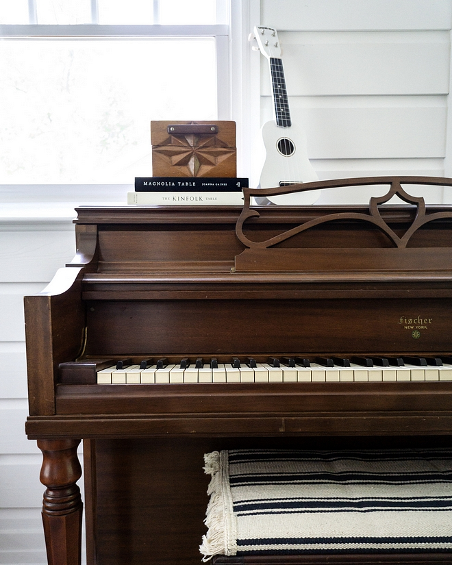 Vintage piano kept in natural color beatiful against white walls