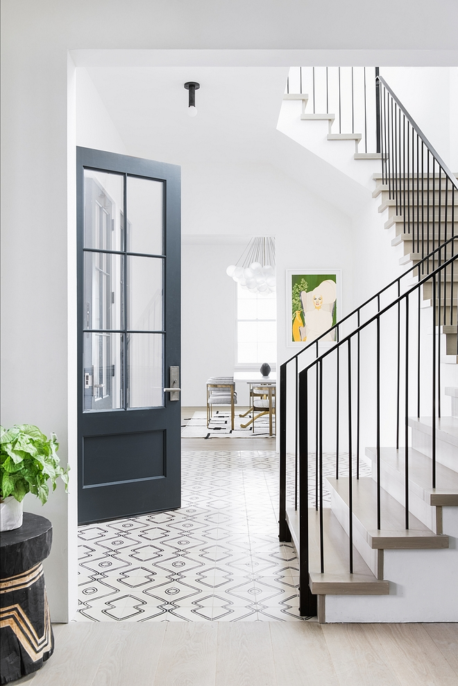 Foyer The tile landing meets the main stairwell which features simple architectural prominence, yet is still remarkably impressionable with the continuation of wood flooring treads, plaster walls, a custom metal railing #foyer #metalrailing #railing