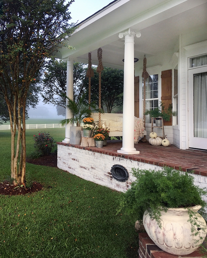 Country home with front porch with swing and brick flooring