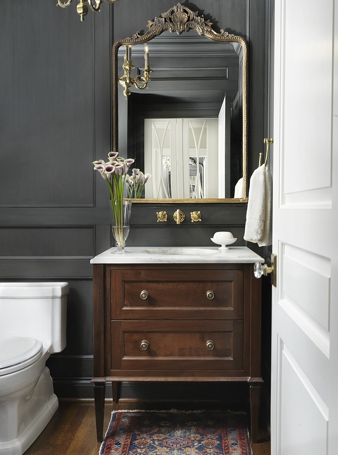 Powder room This chic and classic powder room features a custom furniture-looking vanity with white marble countertop and floor-to-ceiling paneling, painted in a custom charcoal stain color #powderroom