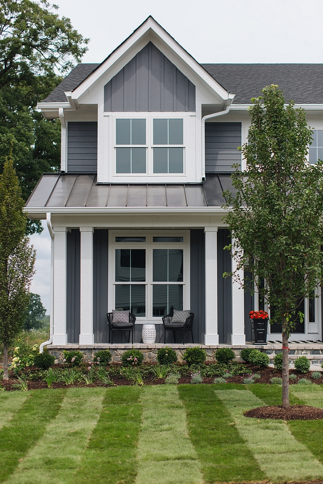 Grey Home Exterior with grey board and batten siding and white trim white porch columns and metal roof #GreyHome #GreyExterior #greyboardandbattensiding