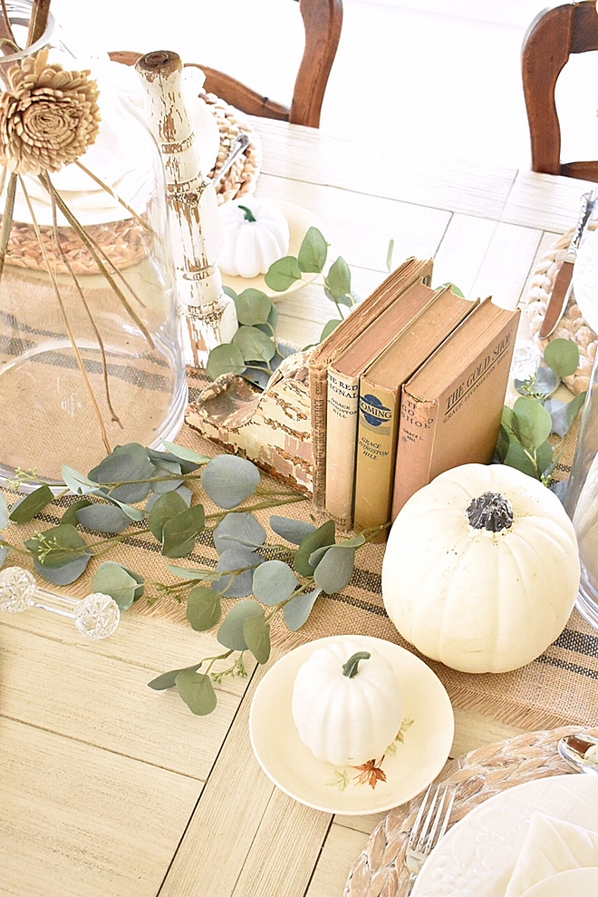 Neutral Fall Tablescape with white pumpkins vintage books and eucalyptus