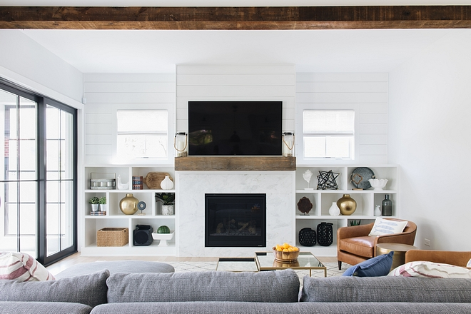 The family room features reclaimed ceiling beam and shiplap above built-ins and mantel #familyroom #reclaimedceilingbeam #shiplap #mantel